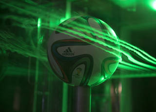 Smoke and lasers show the flow pattern around an Adidas Brazuca soccer ball at NASA's Ames Research Center.
