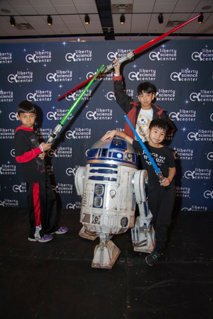 "Visitors pose with R2-D2 Feb.12 at Liberty Science Center's ""Science, Sabers & Star Wars"" event."