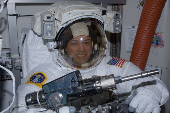 NASA astronaut Ron Garan checks out tools in the International Space Station's Quest airlock prior to the July 12, 2011, spacewalk he performed with crewmate Mike Fossum (not pictured).