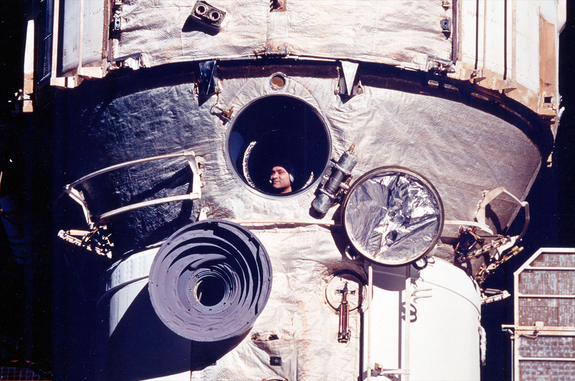 Cosmonaut Valeri Polyakov looks out the Russian space station Mir's window during his record-setting 438-day mission from 1994 to 1995.