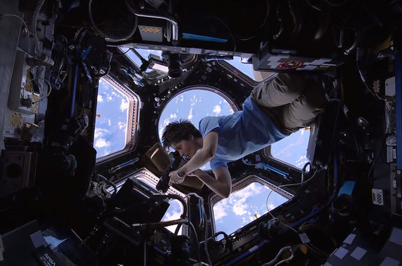"ESA astronaut Samantha Cristoforetti, inside the space station cupola, photographs the Earth in a scene from the IMAX film ""A Beautiful Planet."""