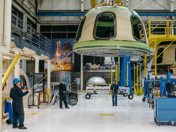 Blue Origin workers move a spacecraft component at the company's Kent, Washington, factory.