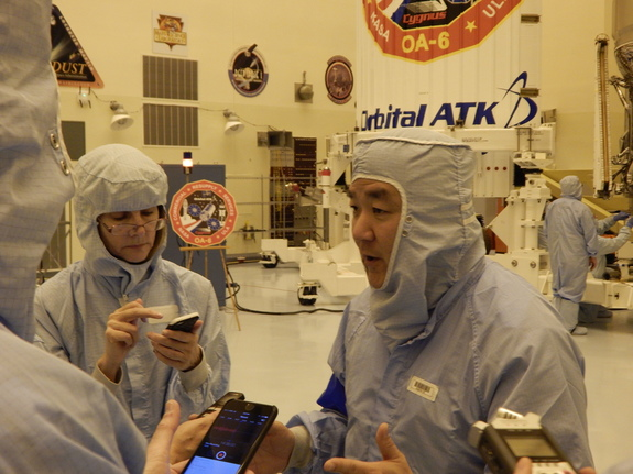 Reporters confer with Orbital vice president Dan Tani in the Kennedy Space Center clean room March 8.