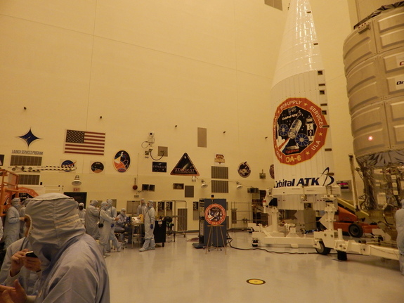 Engineers work to prepare Orbital ATK's Cygnus spacecraft for its March 22 flight; patches from past missions prepared in the Kennedy Space Center clean room are visible on the back wall.