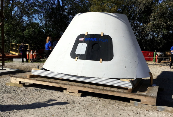 A mock-up of the crew capsule for the reusable CST-100 Starliner, resting under the real Crew Access Arm being built and tested near Kennedy Space Center.
