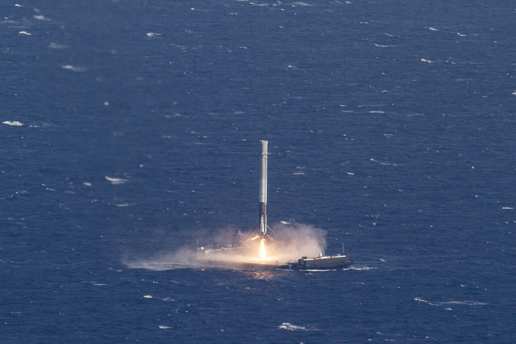 With stunning precision, a SpaceX Falcon 9 rocket touches down on a drone ship landing platform in the Atlantic Ocean after launching a Dragon supply ship into orbit and returning to Earth on April 8, 2016.