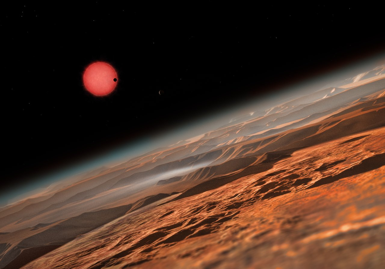 This artist's impression shows one potential view of the TRAPPIST-1 star system as seen from near one of the three alien planets circling the ultracool dwarf star. The three planets are the first ever found around such a tiny and dim star.