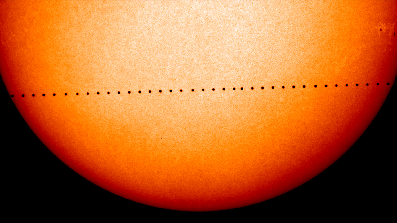 The silhouette of Mercury dotting along the sun