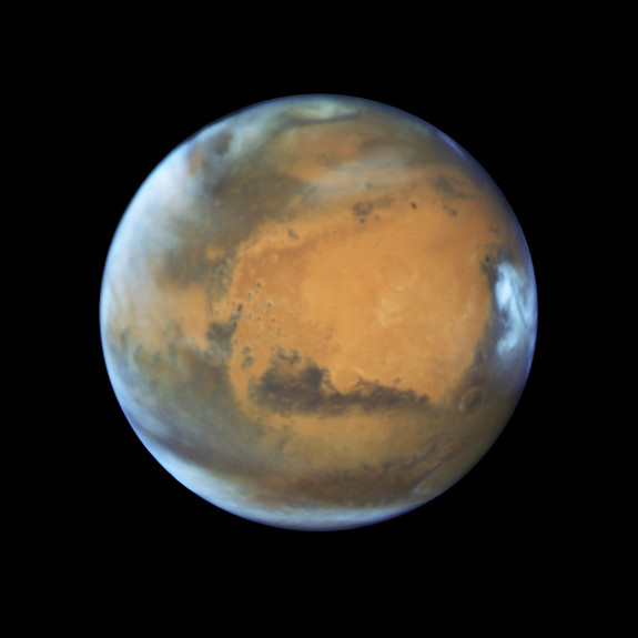 Mars as it was observed shortly before opposition in May 2016 by the Hubble Space Telescope. Some prominent features are clearly visible, including the heavily eroded Arabia Terra in the center of the image and the small southern polar cap.
