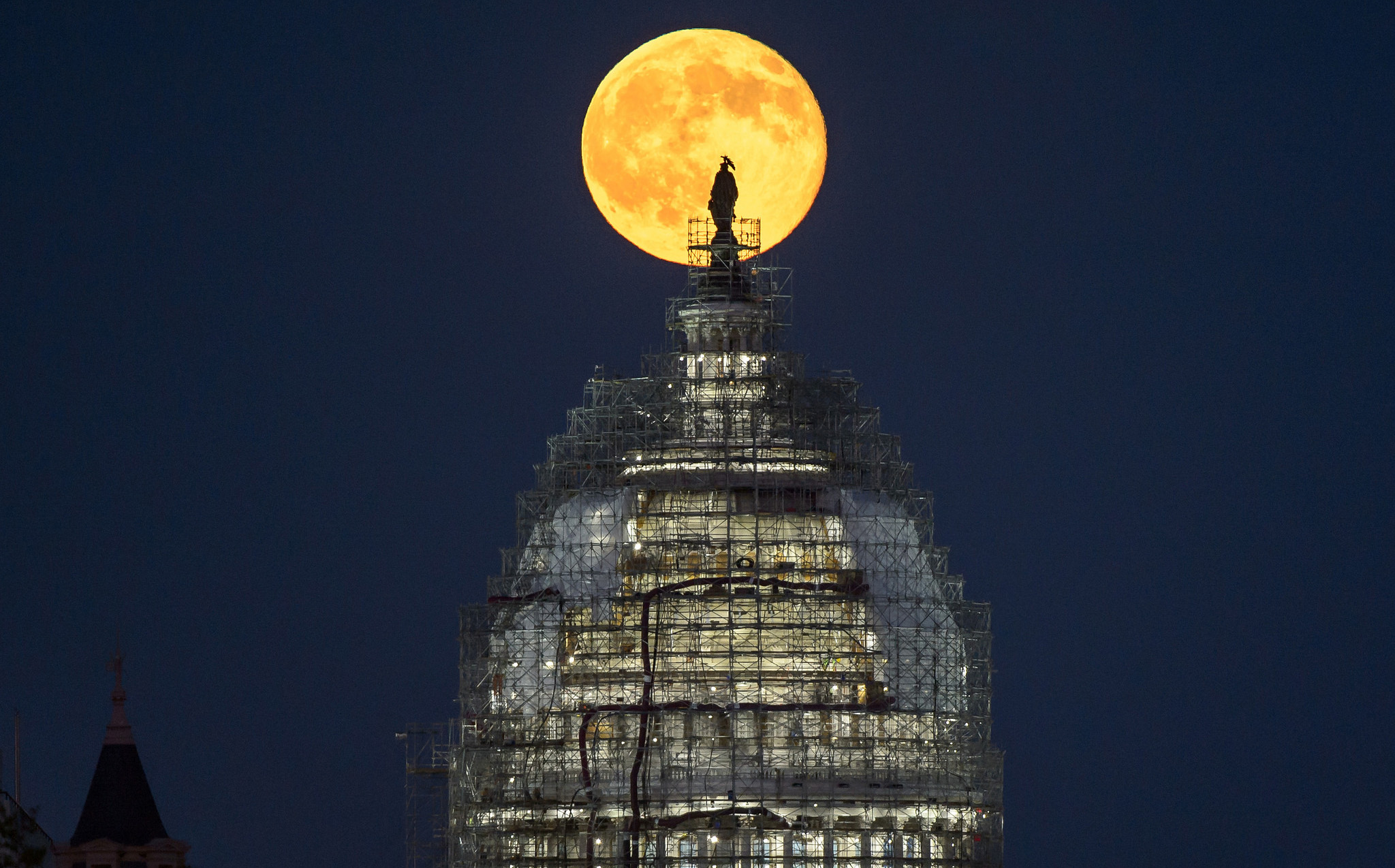 "The ""blue moon"" full moon of July 31, 2015 rises behind the dome the U.S. Capitol in this image from NASA photographer Bill Ingalls. The May 21, 2016 full moon is the fourth full moon in spring, which is also known as a ""blue moon."""