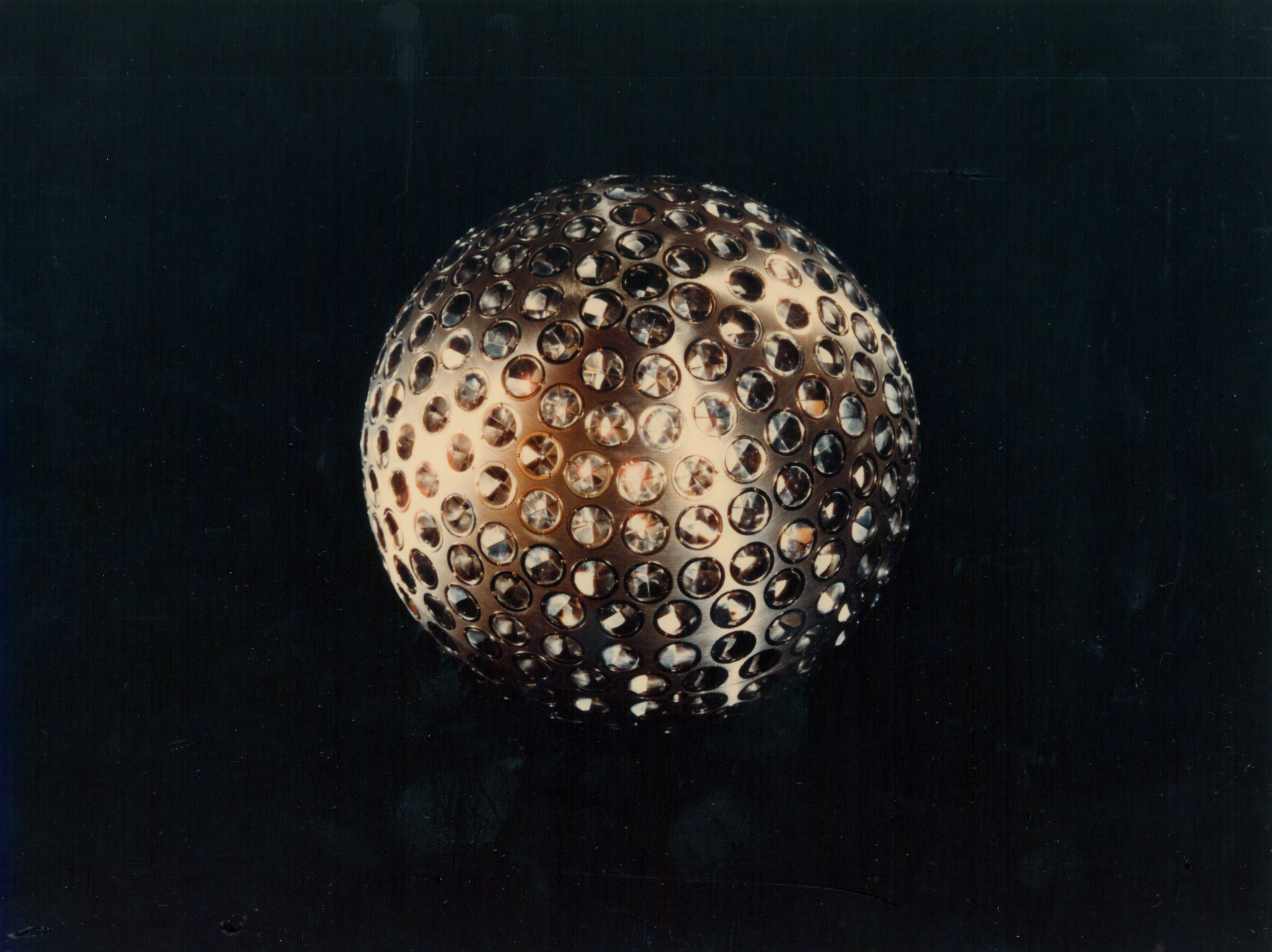 Metallic ball regularly pockmarked with prisms