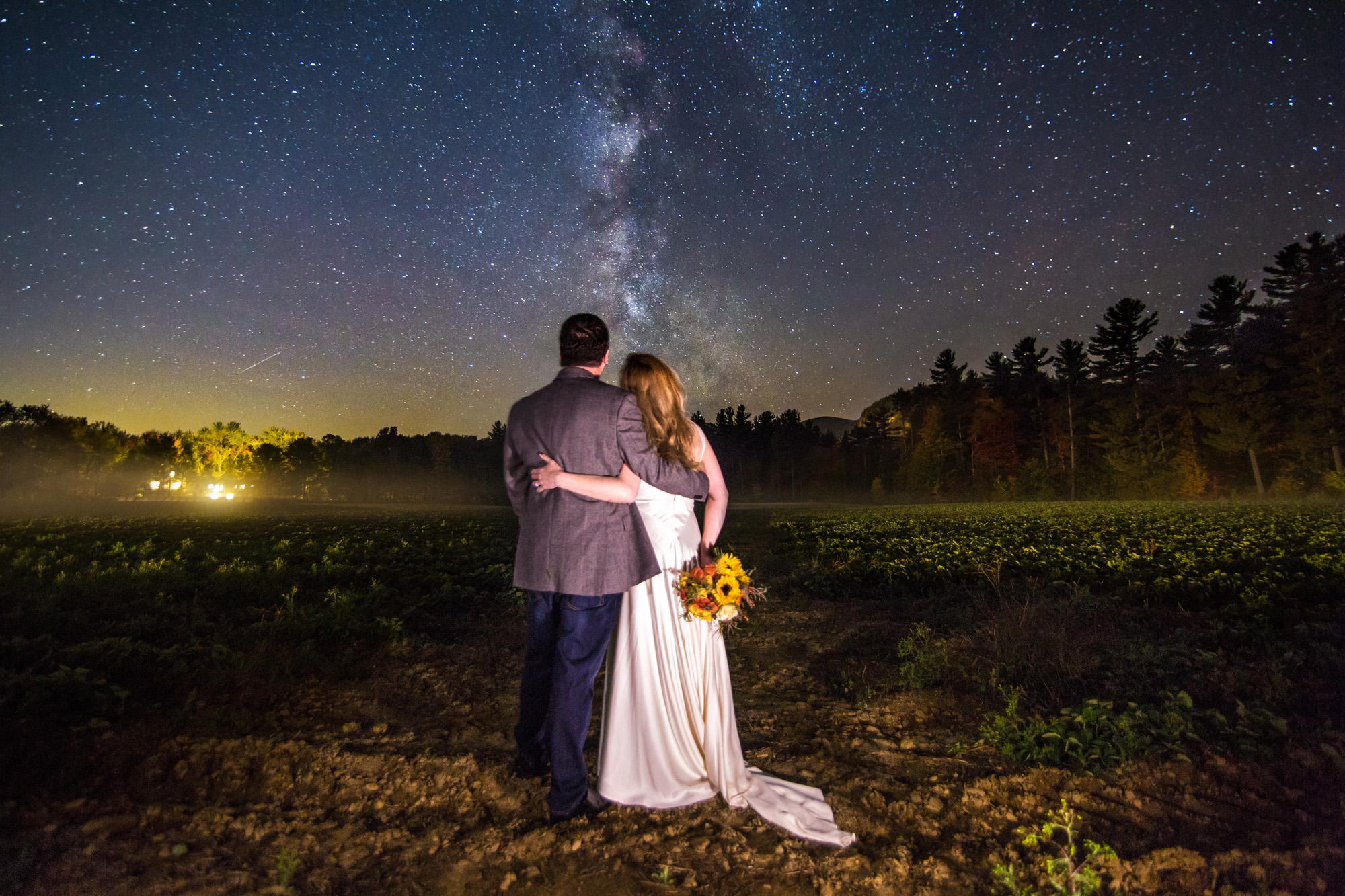 A bride and groom pose for a wedding photo with the Milky Way in the Wight Mountains of New Hampsire.