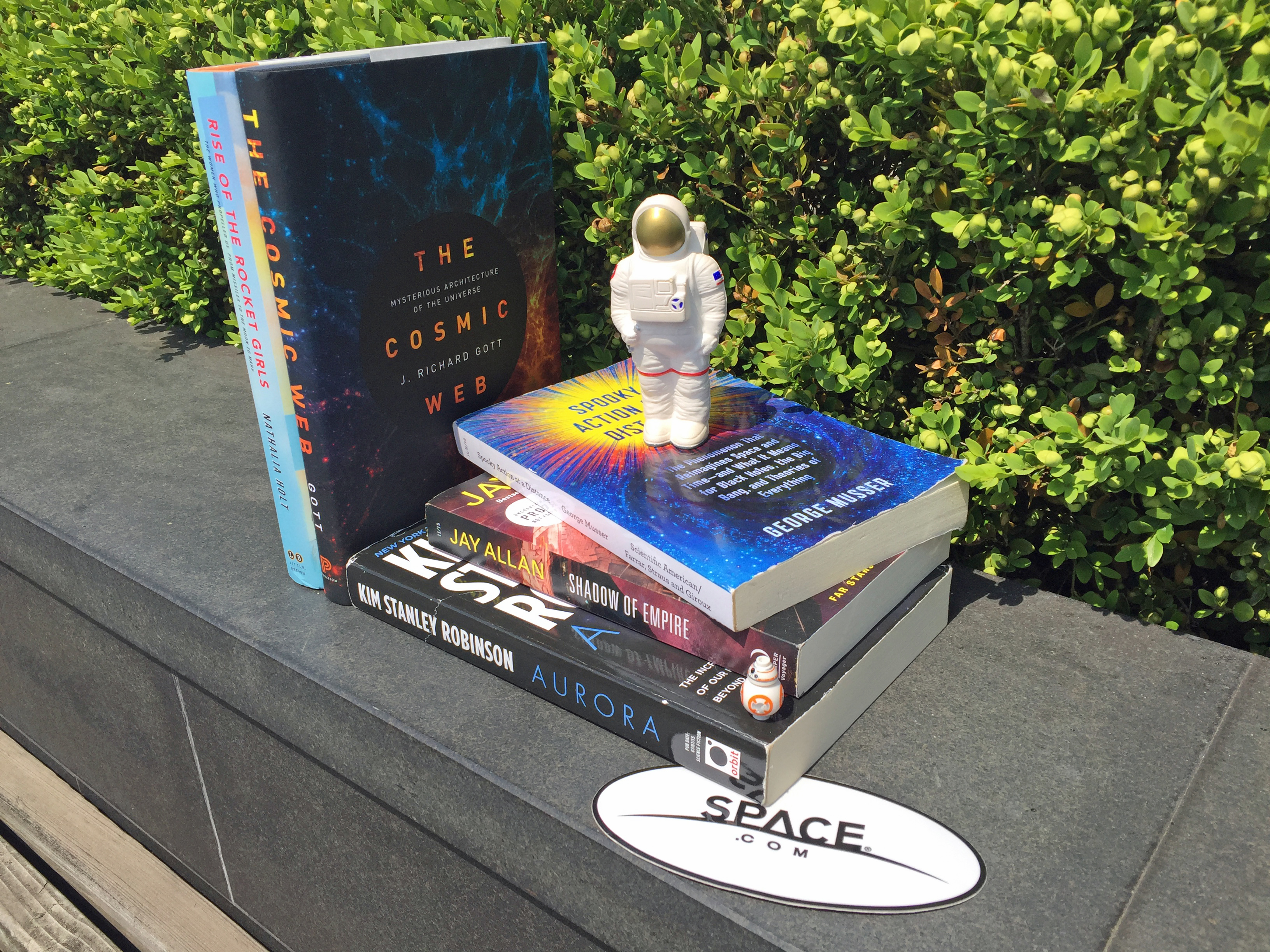Stack of books with toy astronaut outside