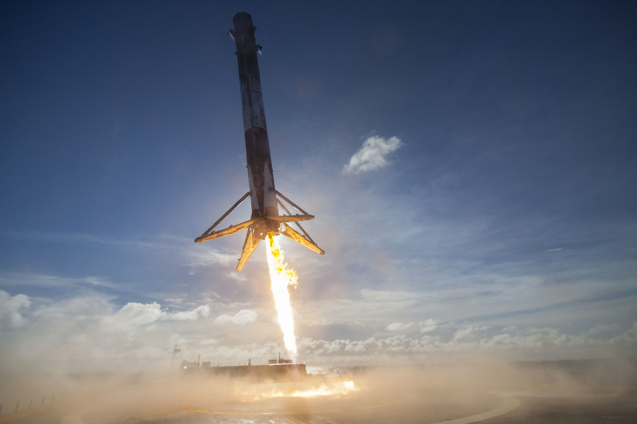 "The first stage of a SpaceX Falcon 9 rocket comes in for a successful landing on the drone ship ""Of Course I Still Love You"" after launching the Thaicom 8 satellite into orbit on May 27, 2016. SpaceX hopes to refly a used Falcon 9 booster in September or"