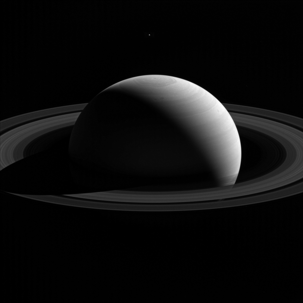 A new image captured from NASA's Cassini spacecraft shows Saturn's moon Tethys lingering above the planet's north pole.