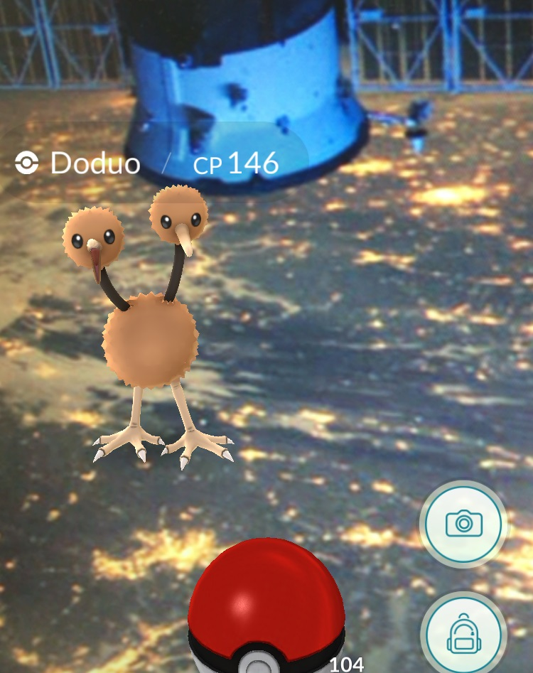 A computer-animated Pokemon, a bird with two heads, floats over an image shot from the International Space Station in a smartphone interface