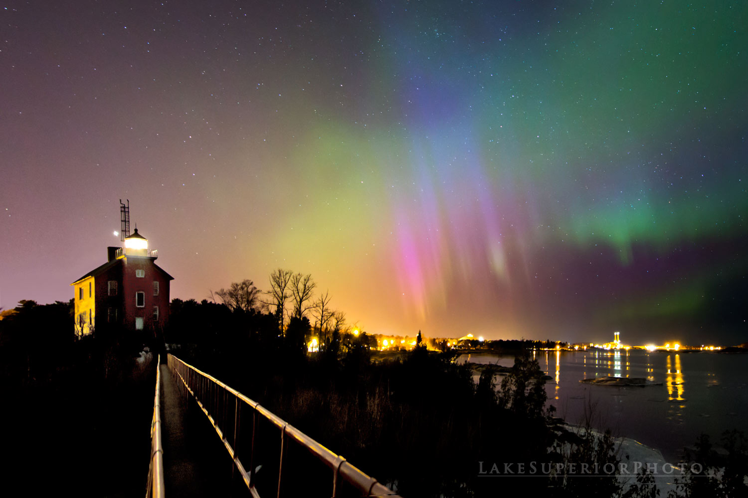 Rainbow-colored northern lights glisten above a lighthouse on the shore of Lake Superior.