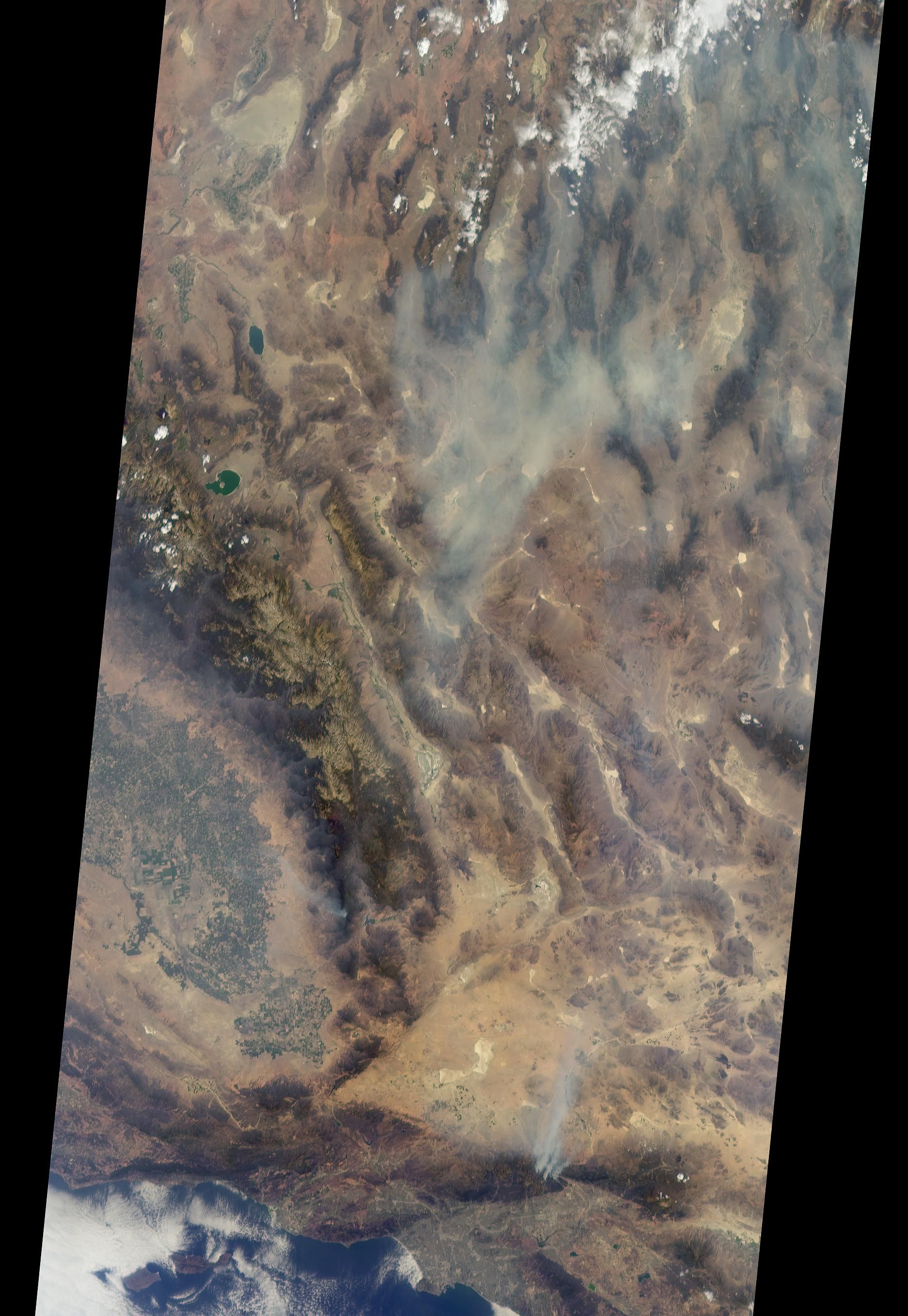 Natural-color satellite image of the Blue Cut wildfire in Southern California midday on Aug. 17, 2016. Los Angeles is pictured by the coast, with three smoke plumes rising in the north.