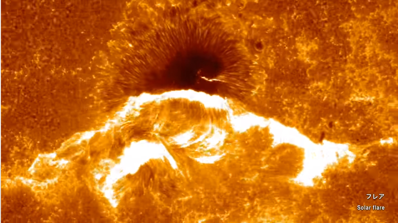 A spectacular solar flare erupts near a huge sunspot on the surface of the sun in this view from the Japanese Hinode solar observatory.