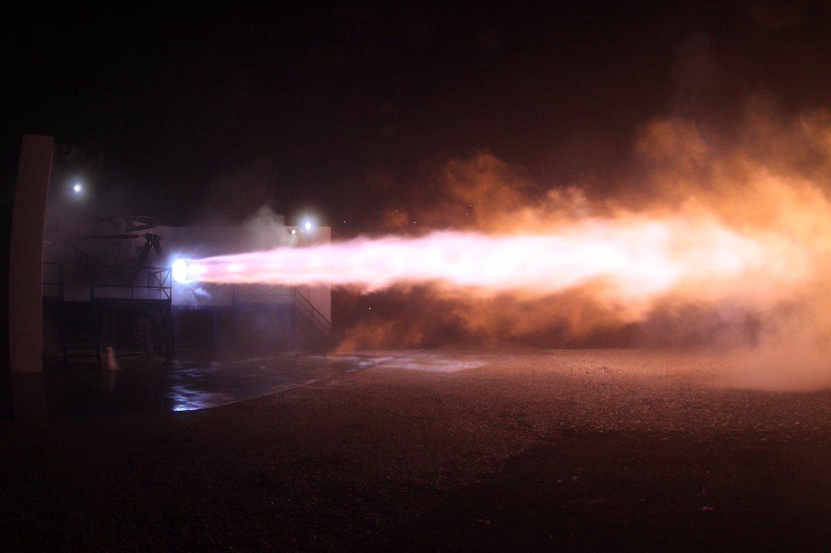A large rocket engine blasts a jet of fire horizontally.