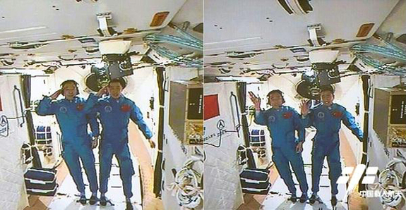 Astronauts Jing Haipeng and Chen Dong, the crew of China's Shenzhou-11 mission, salute and wave from inside the country's Tiangong-2 space laboratory after arriving at the mini space station on Oct. 18, 2016. The astronauts are flying a 30-day mission to the space lab, China's longest human spaceflight yet.