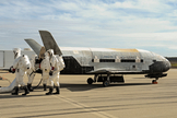 Recovery crewmembers process the X-37B Orbital Test Vehicle at Vandenberg Air Force Base in California after the robotic space plane touched down in October 2014.