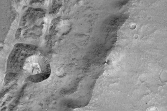 Image of a 0.9 mile-size (1.4 kilometers) crater (left-center) _n the rim of a larger crater near the Mars equator. It was acquired at 7.2 meters/pixel by the Colour and Stereo Surface Imaging System (CaSSIS) aboard the European Space Agency's ExoMars Trace Gas Orbiter.
