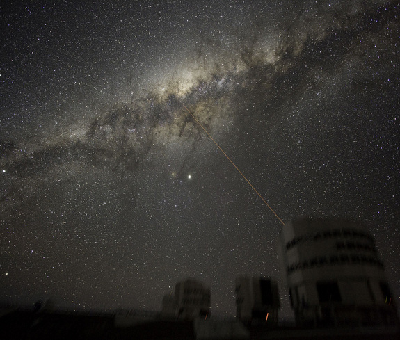 Three of the four 8.2-m telescopes forming ESO's VLT are seen dimly, with a laser beaming out from Yepun, Unit Telescope number 4. The laser points at the Galactic Center of the Milky Way, our galaxy. The bright object at center is Jupiter, while the othe