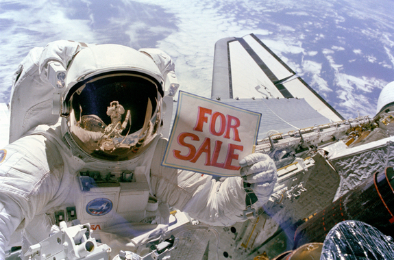 "Astronaut Dale Gardner holds up a ""For Sale"" sign, referring to the two satellites, Palapa B-2 and Westar 6, that they retrieved from orbit. Astronaut Joseph Allen IV is reflected in Gardner"